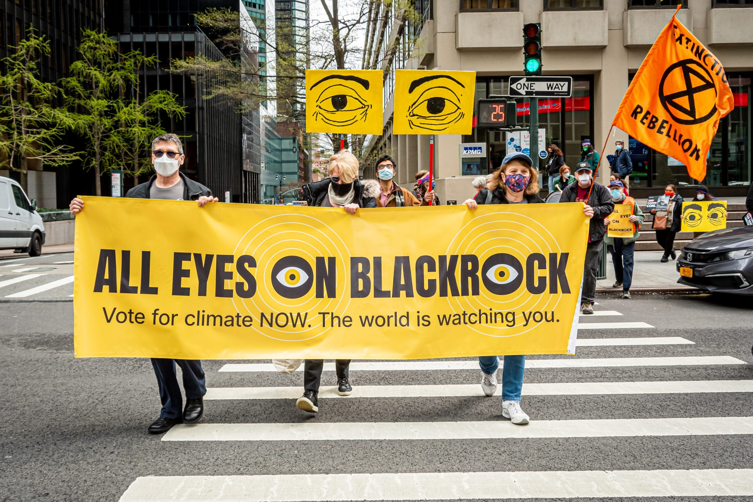 Climate activists march with a banner that says 'All Eyes on BlackRock' in new york city